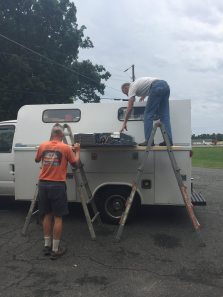 After some brainstorming on how to get it up on the roof, they decided to put it on top of the roof, Cecil offered to put it on top of his service truck!