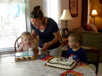 """Our daughter lighting their birthday candles. The two year old didn't want to put on his """"birthday tee-shirt"""" he decided to wear his birthday suit! LOL"""